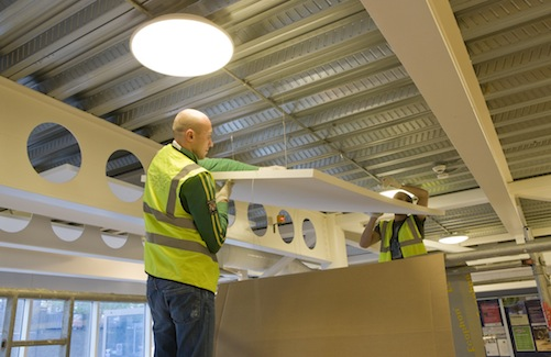 Acoustic installers attaching sound absorbing panels to cafe ceiling