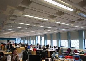 Acoustic baffles shown suspended from open plan office ceiling.