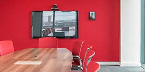 video conferencing room with red chairs and red fabric acoustic wall.