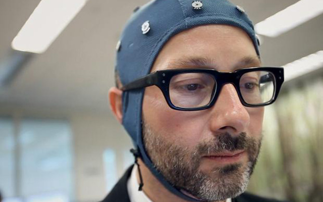 Man wearing cap measuring brain activity for office experiment