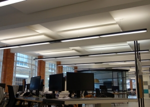 Open plan office showing ceiling panels within lighting.