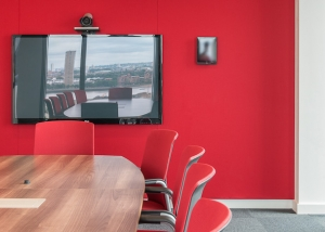 Video conferencing meeting room with table and chairs and VC equipment. Red wall at far end.