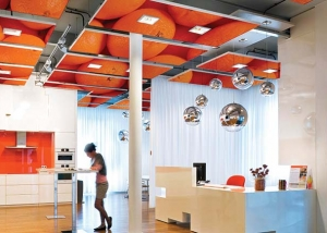 Open plan kitchen with orange artwork on printed acoustic ceiling panels.