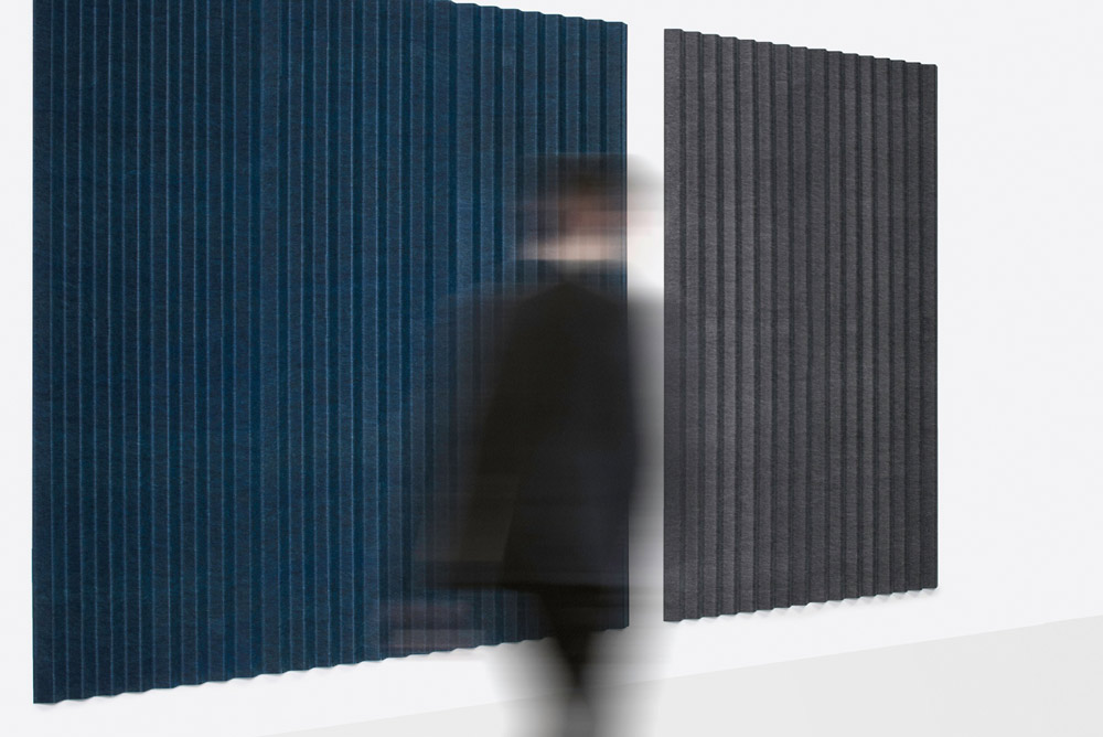man walking past acoustic panels on wall